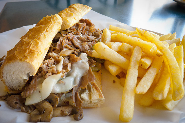 This Provolone cheese steak is busting at the seams. Even the fries can't keep their hands off it.