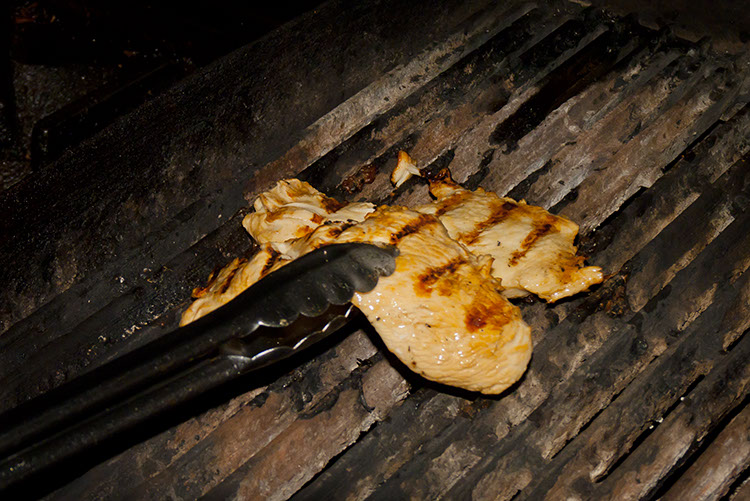A perfectly plump chicken breast is plucked from the flame-broiler.